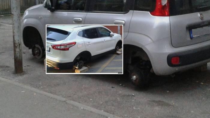 furto di pneumatici due auto lasciate sui mattoni foto